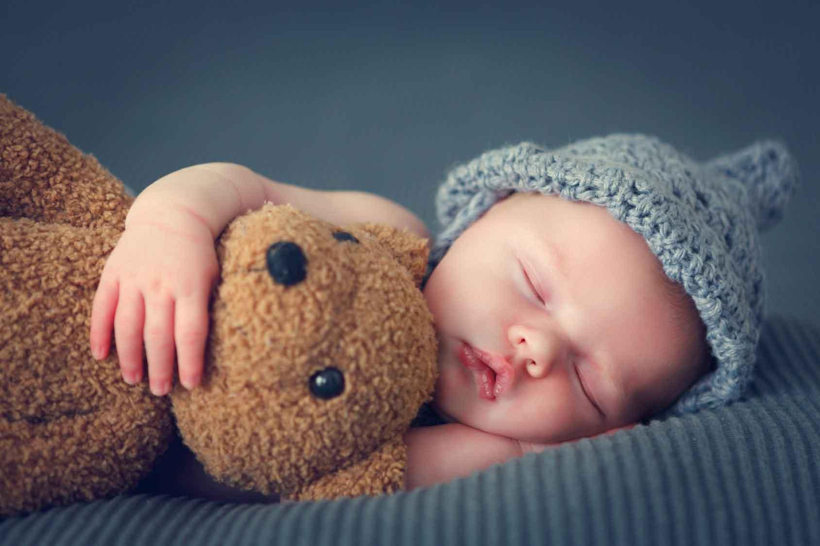 Baby schläft mit Teddybär