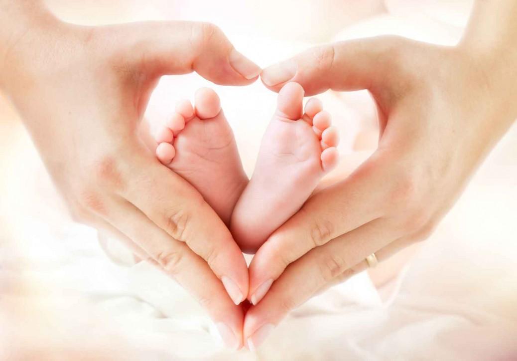 Mutter zeigt Herz mit den Händen um Babyfüsse